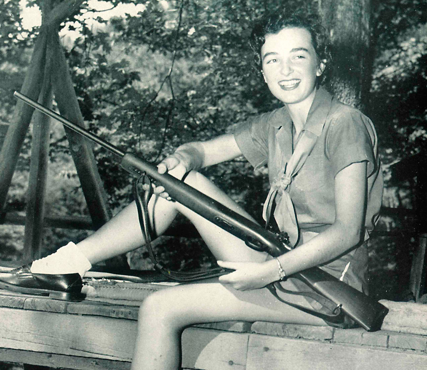 girl posing with rifle at camp