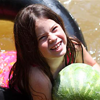 camp girl swimming with a watermelon