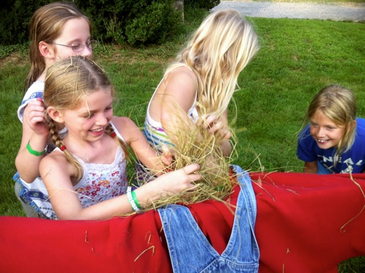 stuffing hay into a scarecrow