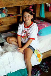 Girl sitting on her camp bunk bed