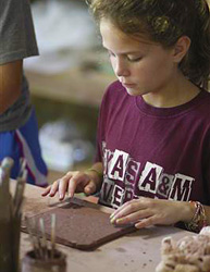 Girl works on clay slab in camp ceramics class
