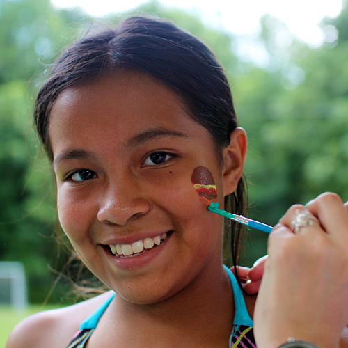 Camp girl having face painted