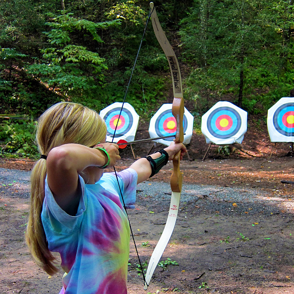 Girl shooting archery at summer camp