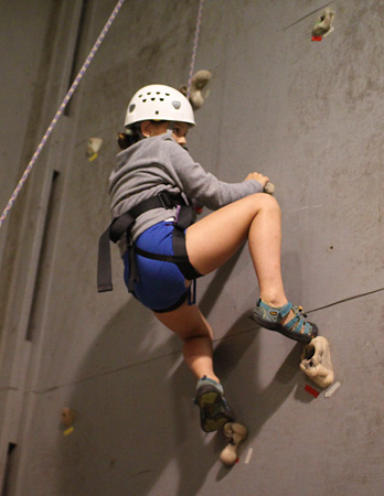 Rock climbing girl on wall in gym