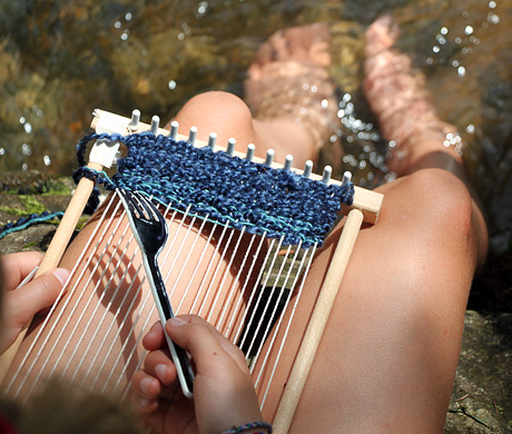 Camp girl using lap loom with feet in creek