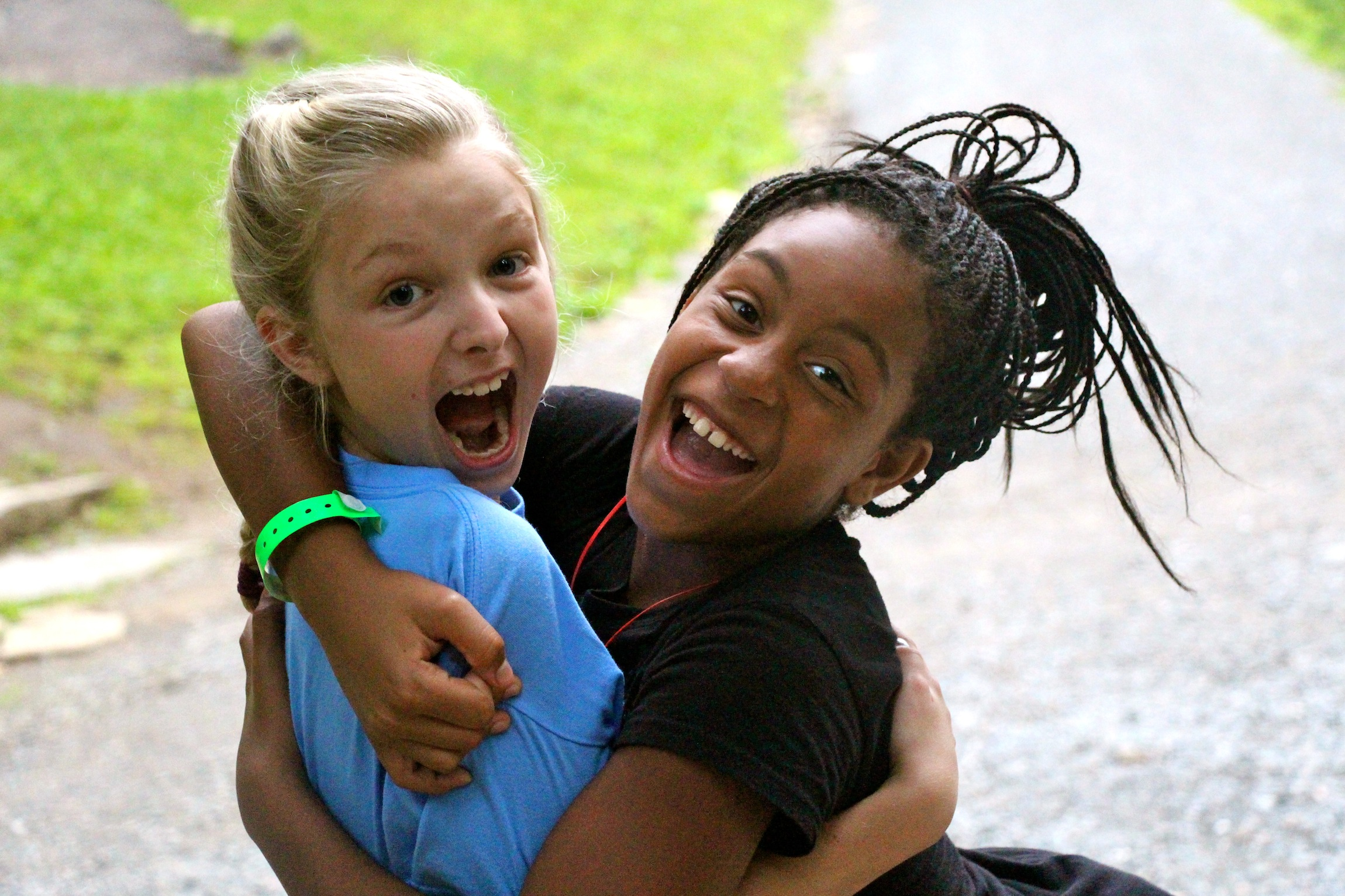 white and black camp kids hugging