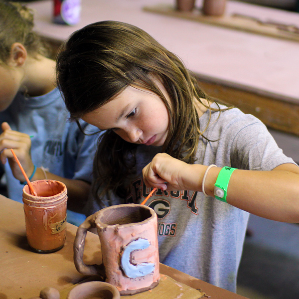 Pottery Glazing child at summer camp