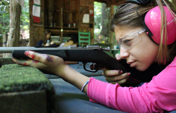 camp girl aiming a rifle