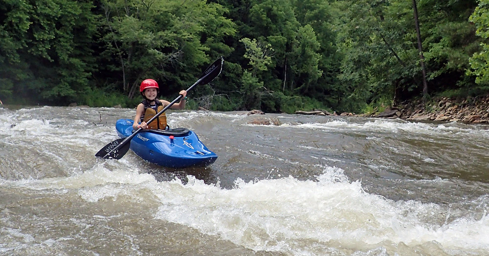Girl kayaking in whitewater