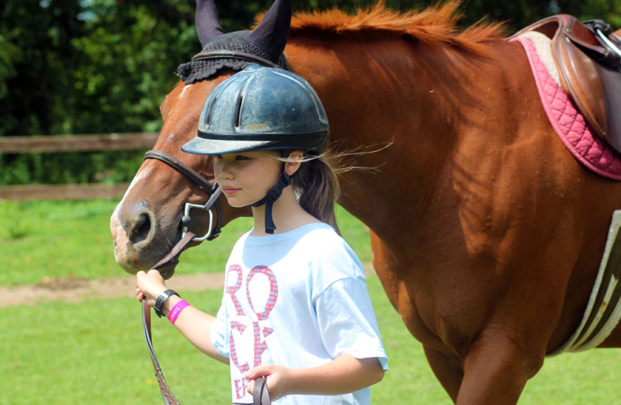 girl leading horse at camp
