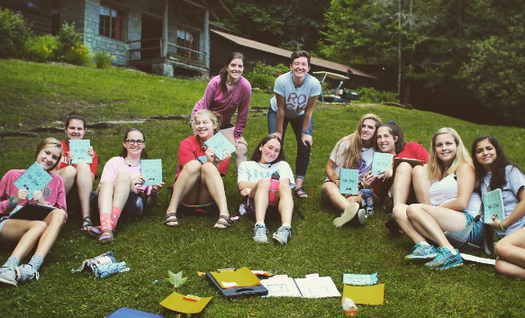 camp friends sitting in camp chairs