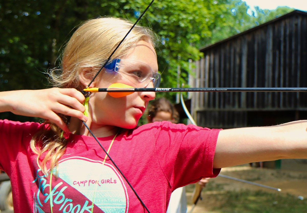 camp girl pulling archery bow
