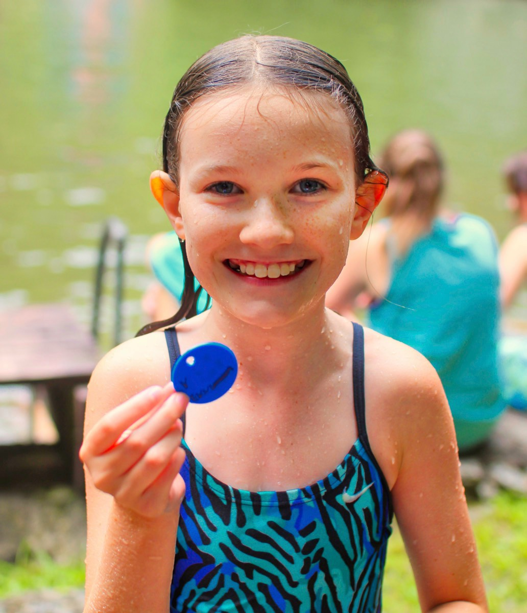 Girl with buddy tag after completing camp swim test