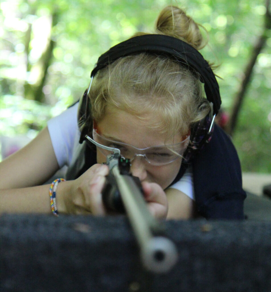 girl aiming rifle at target