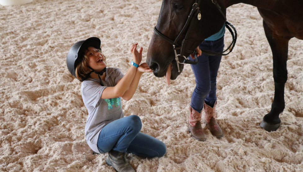girl laughing with horse