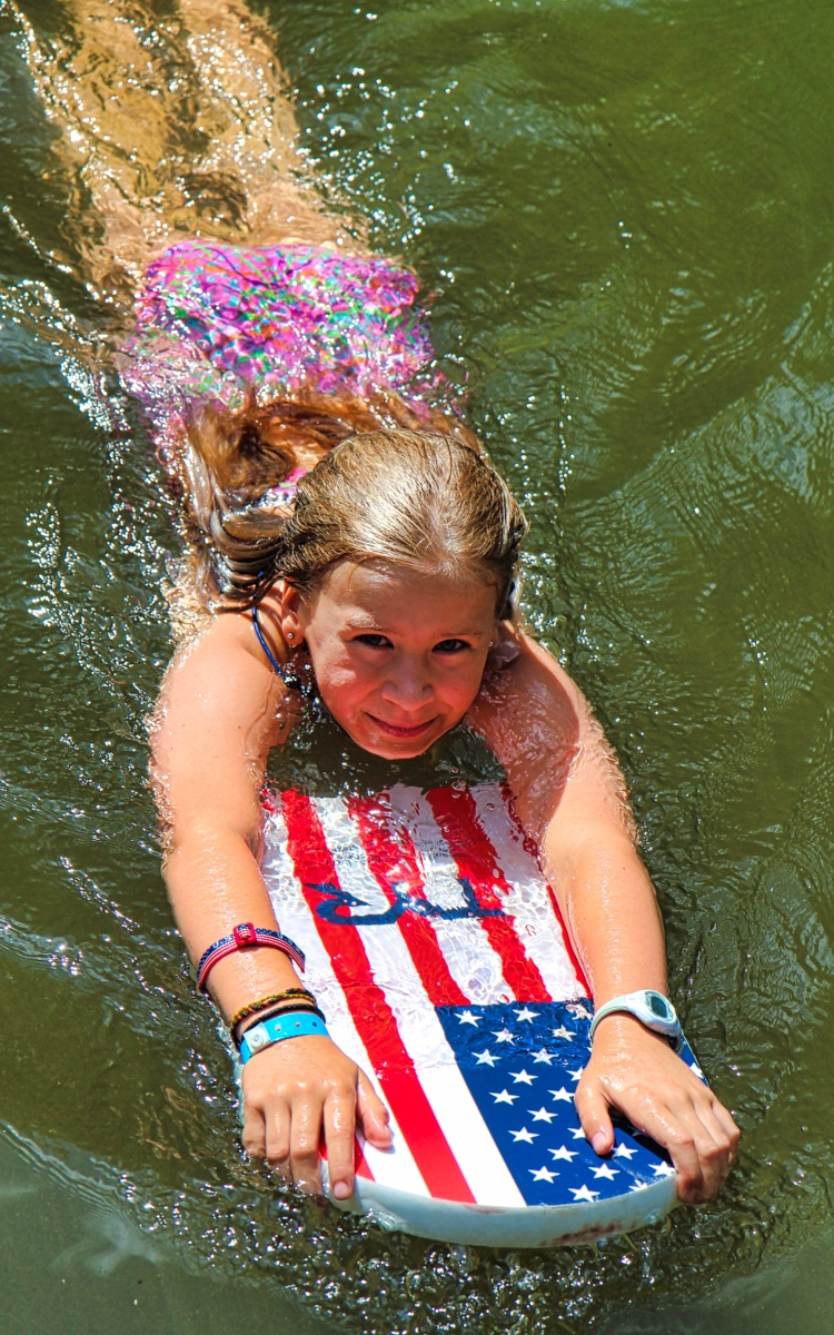 Child swimming with kick board at camp