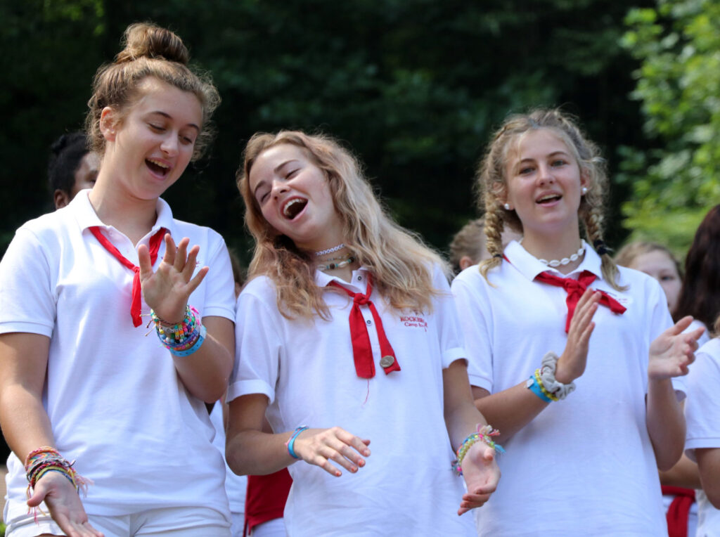 three teen girls in camp uniforms
