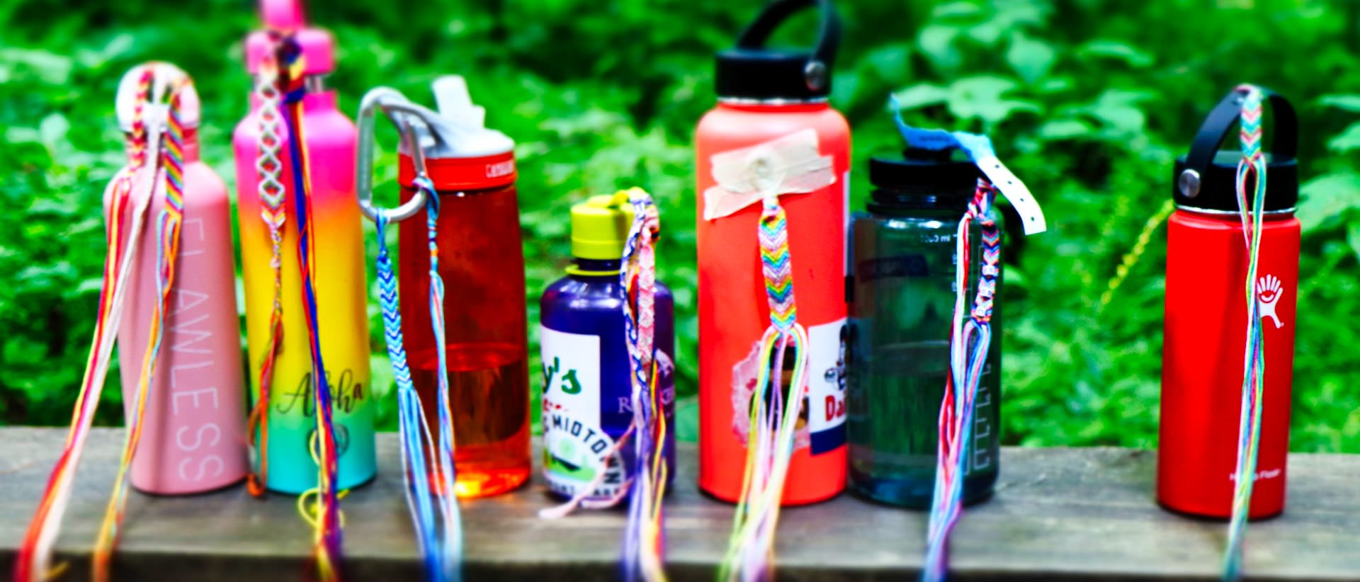 row of camp water bottles with friendship bracelets tied on