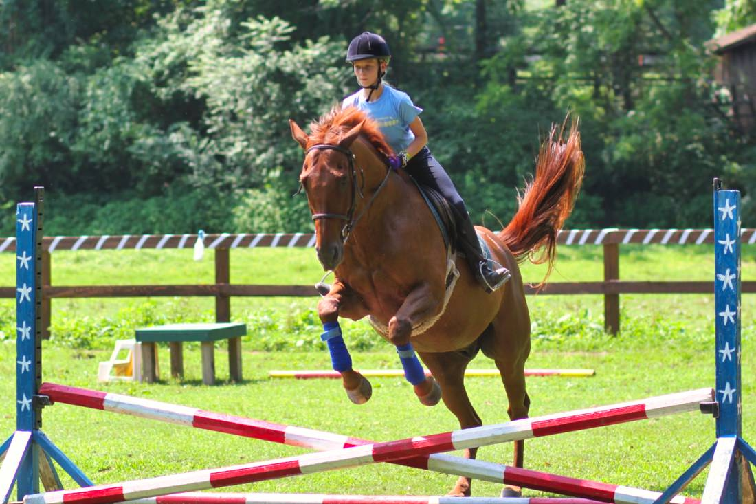 girl jumping a horse at summer camp