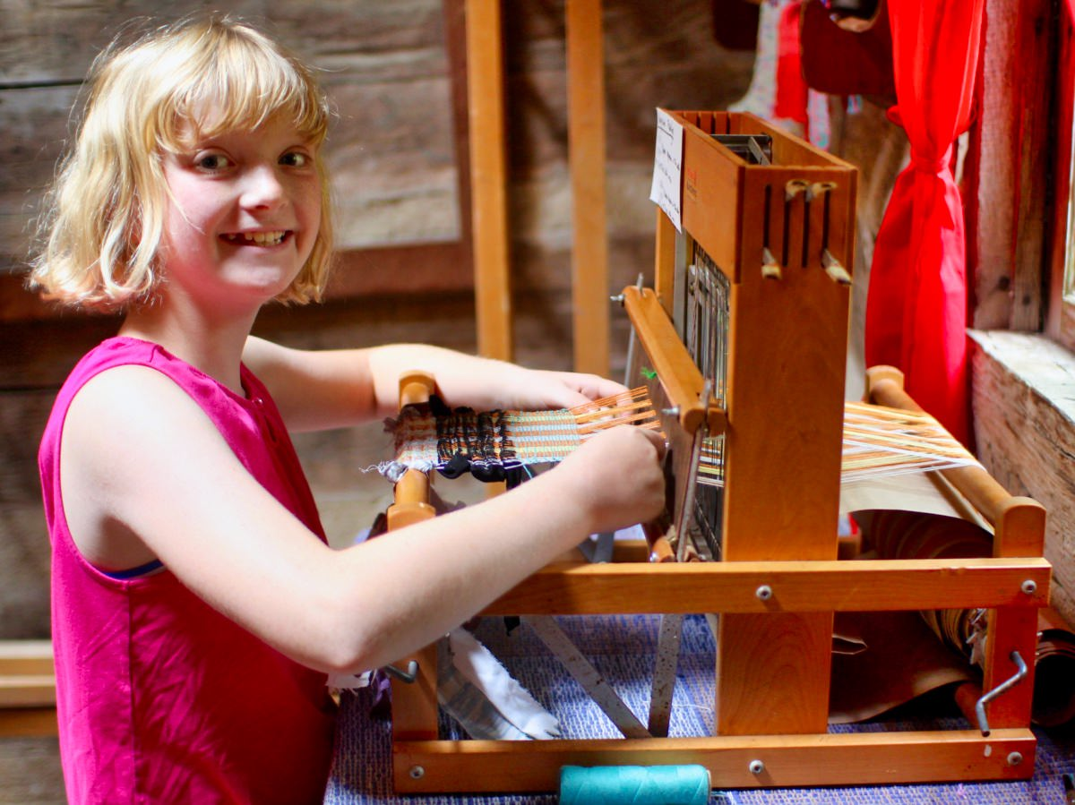 girls camp weaving crafts on a loom