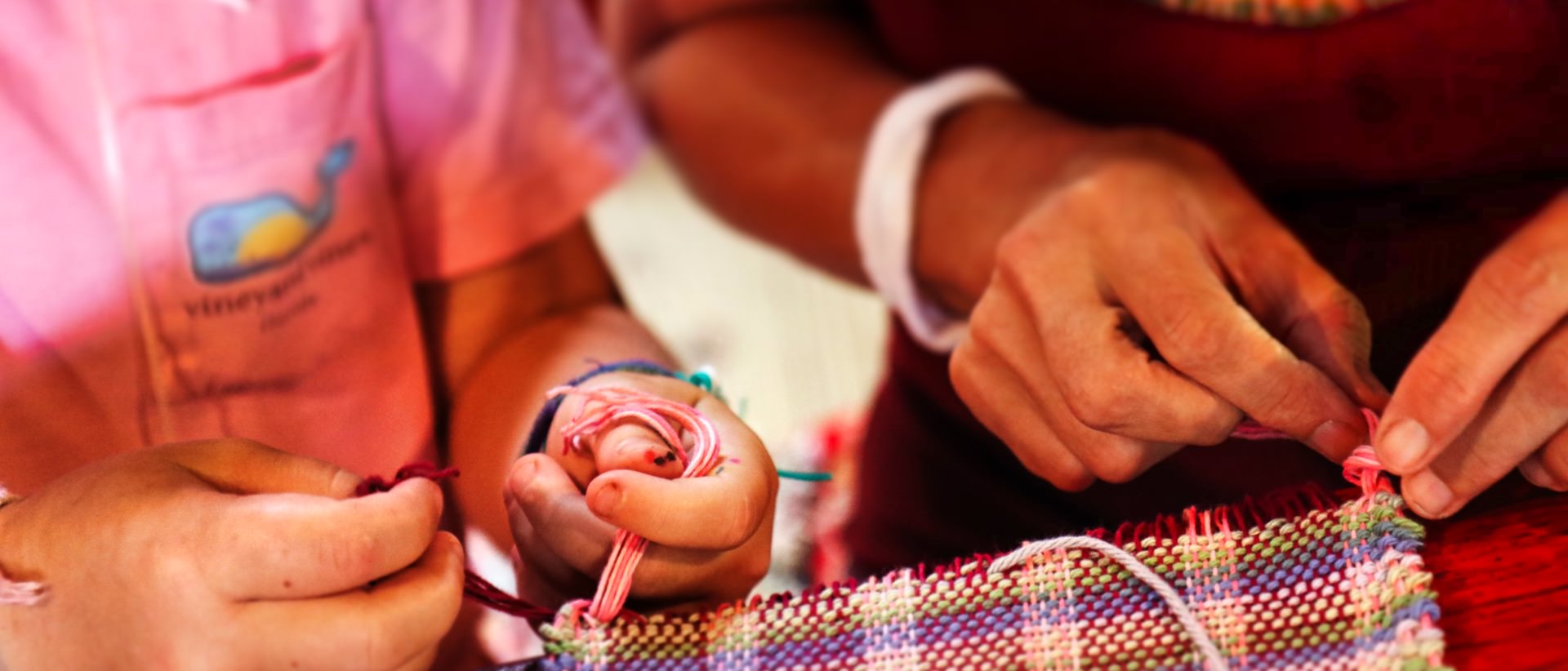 staff helping girl tie weaving