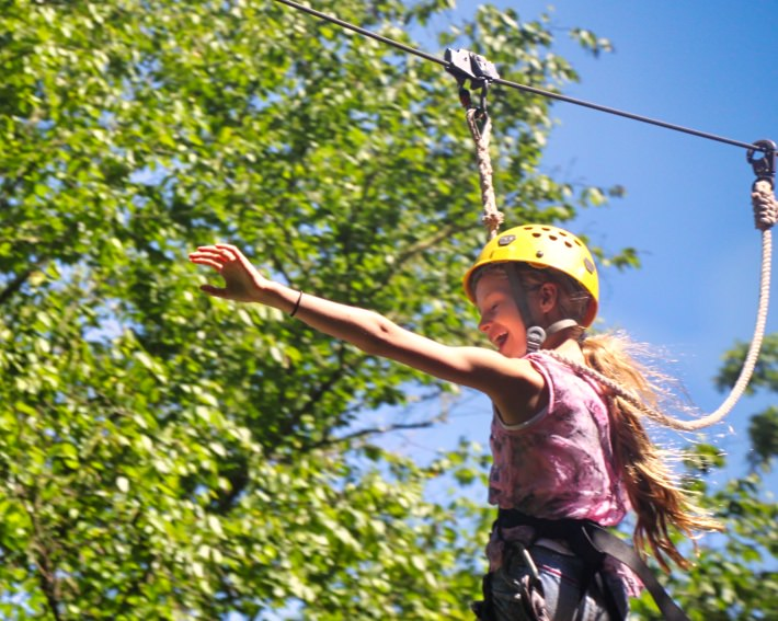 camp girl zip lining outdoors in the trees