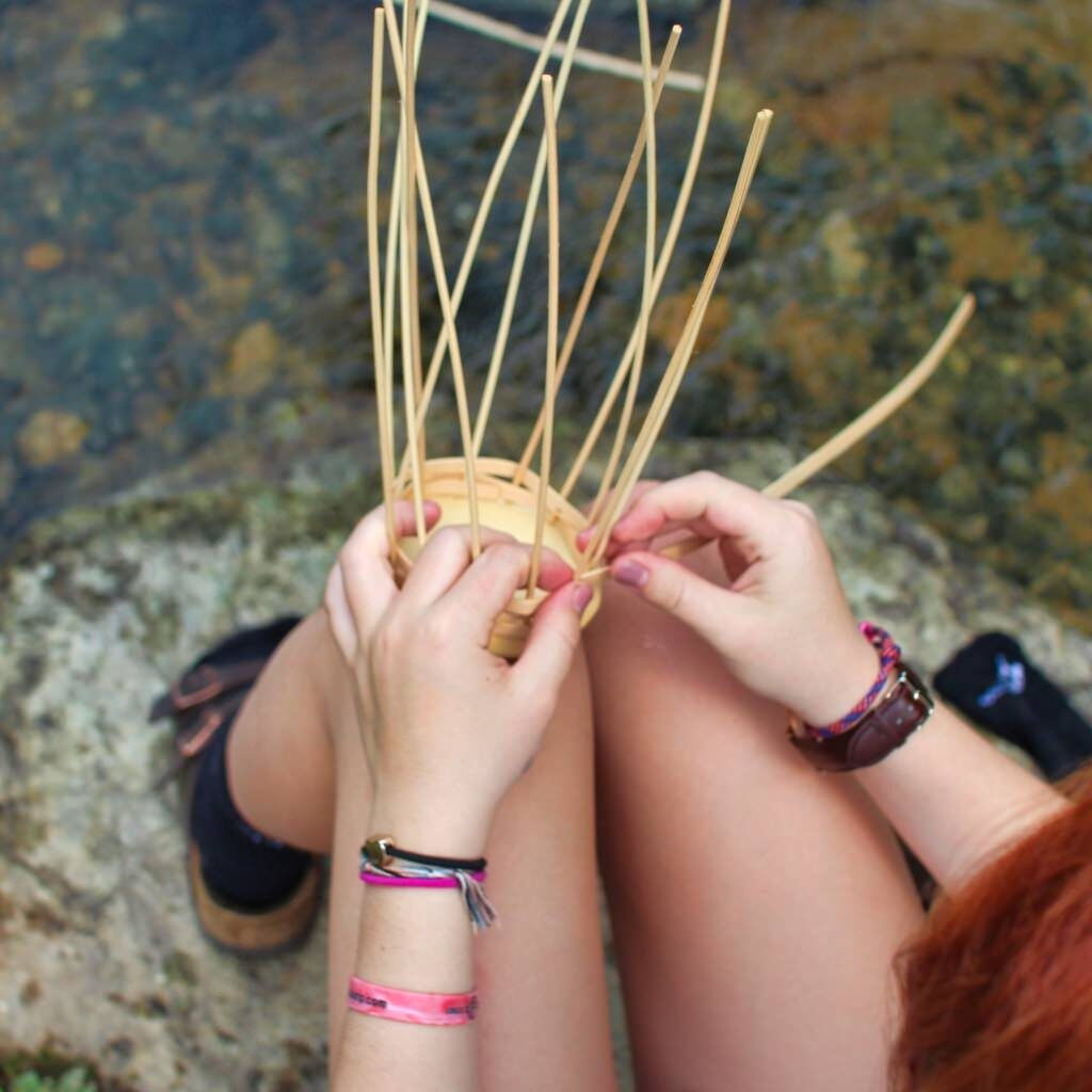 weaving a basket with feet in the creek