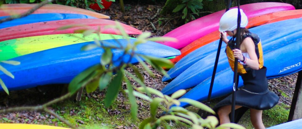 camp girl and row of whitewater kayaks