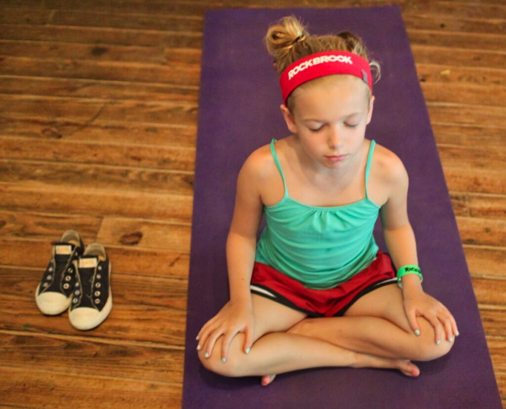 child doing yoga pose at summer camp