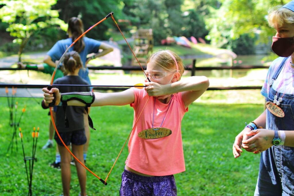 girl learning archery at camp