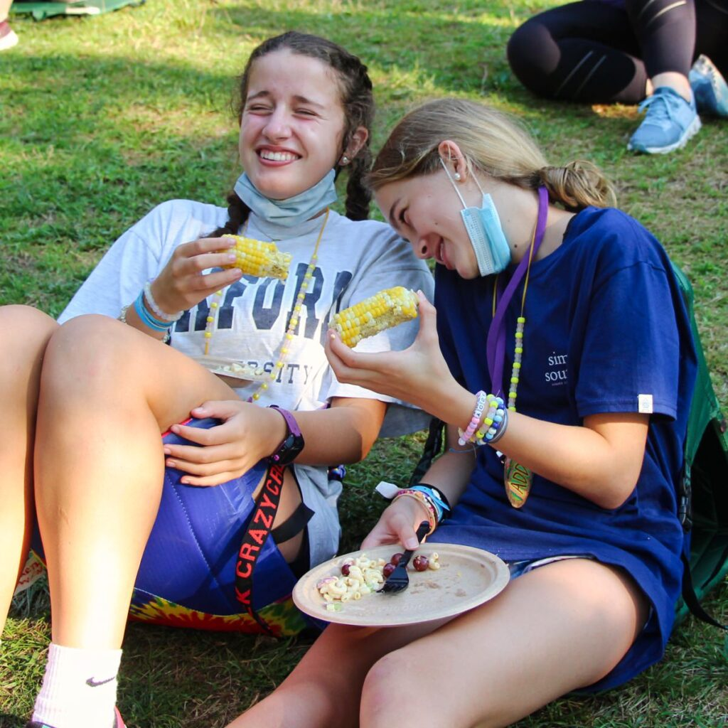 two girls eating picnic dinner at camp