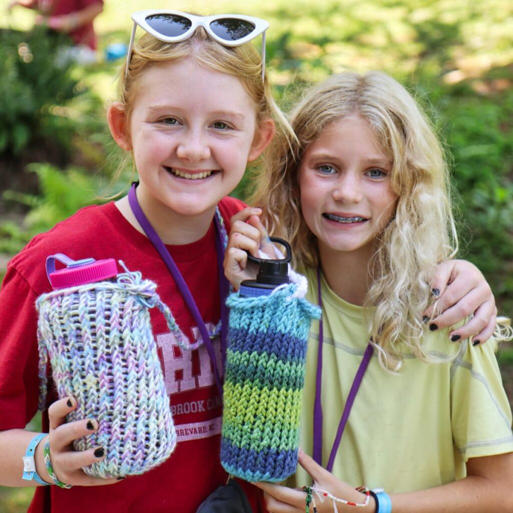 camp girls showing their knitted water bottle covers
