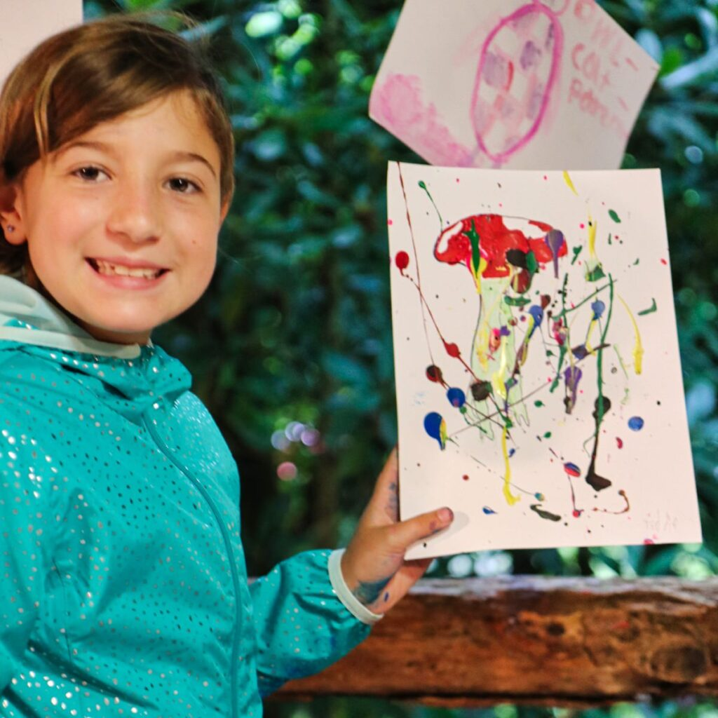 young girl displaying her painting