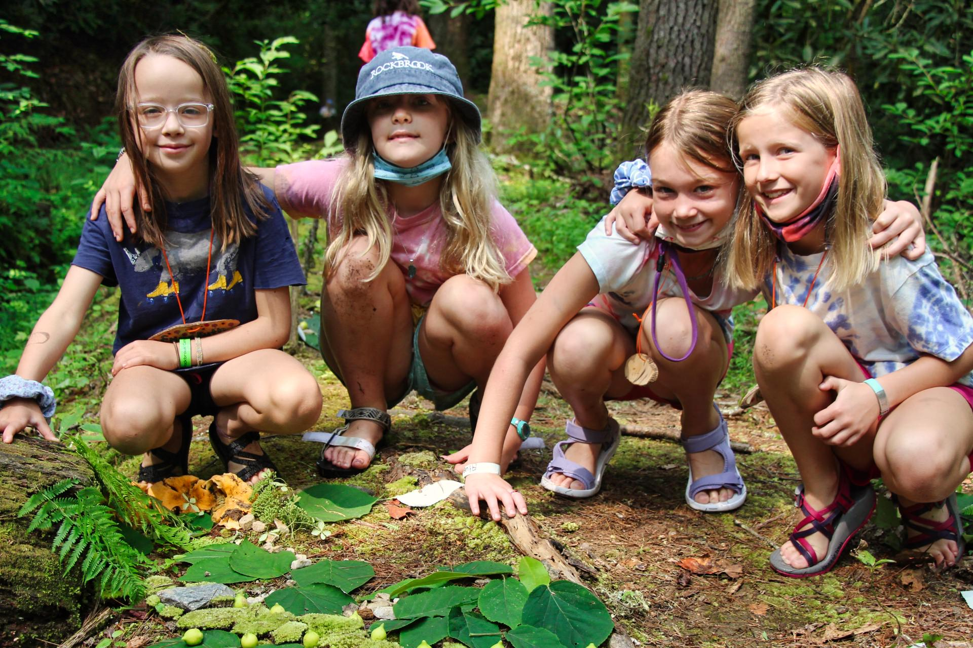 small camp girls building fairy houses